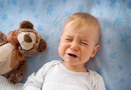 crying boy: Un año de edad bebé acostado en la cama con un oso de peluche de felpa