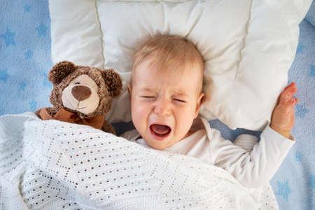 bebe enfermo: Un año de edad bebé llorando en la cama con un oso de peluche Foto de archivo