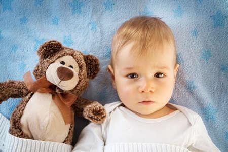 1 歳の赤ちゃんぬいぐるみテディベアと一緒にベッドで横になっています。 写真素材