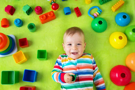 baby toys: Baby boy lying on green blanket with many toys around Stock Photo