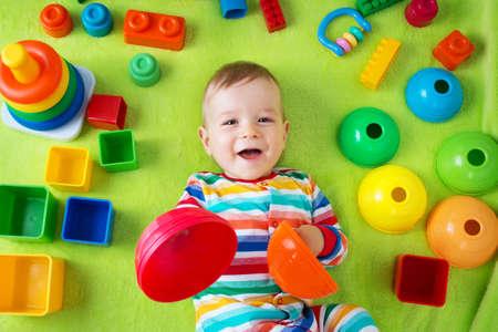 Baby auf grünen Decke mit vielen Spielsachen herumliegen