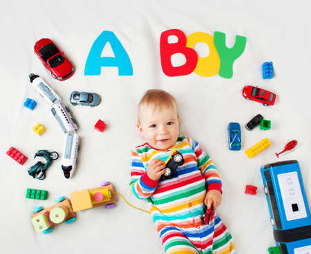 Baby boy lying on soft blanket with letters above Standard-Bild