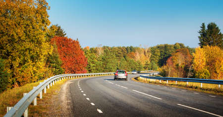 road autumnal: cars moving on a highway road in autumnal landscape Stock Photo