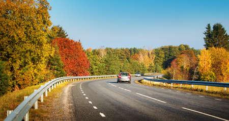 Coches en movimiento en un camino de la carretera en el paisaje otoñal Foto de archivo - 47192126