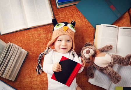 1 year old: One year old baby in owl hat reading books with teddy bear