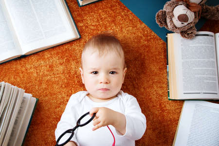 specs: One year old baby among books with spectackles and a teddy bear
