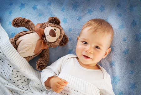baby bed: One year old baby lying in bed with a plush teddy bear Stock Photo