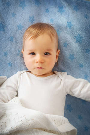 one year old: One year old baby lying on blue towel with stars Stock Photo