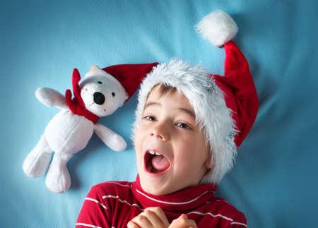 reir: Feliz niño en el sombrero de Papá Noel con un oso blanco en manta azul
