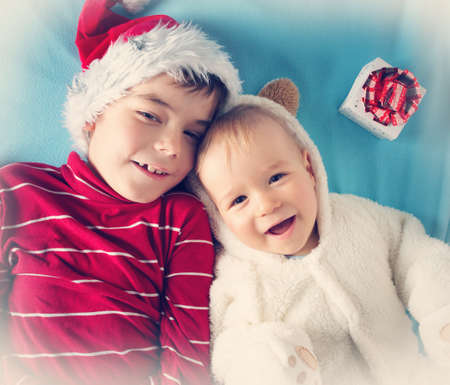 six years: Two brothers, one and six years old in santa and bear costumes lying on blue blanket