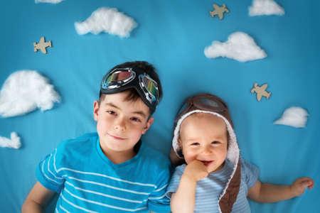 piloto: Dos niños que mienten en la manta con nubes blancas en el sombrero y gafas de piloto