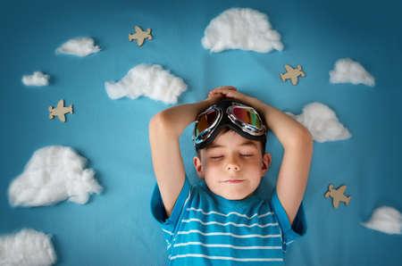 Junge auf einer Decke mit weißen Wolken in Pilotenbrille liegend
