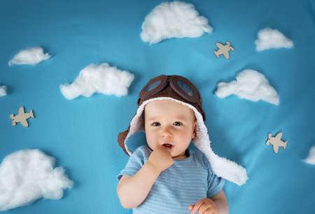 menino deitado no cobertor com as nuvens brancas no chapéu piloto Banco de Imagens