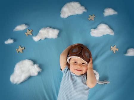 jongen liggend op deken met witte wolken in proefhoed Stockfoto