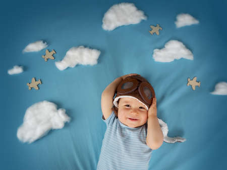 boy lying on blanket with white clouds in pilot hat