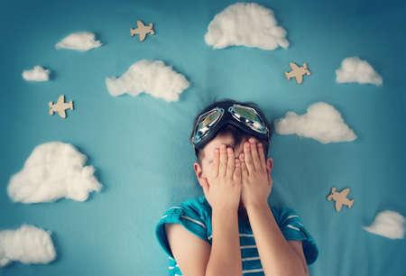 enfant qui dort: garçon allongé sur une couverture avec des nuages ??blancs dans des verres pilotes Banque d'images