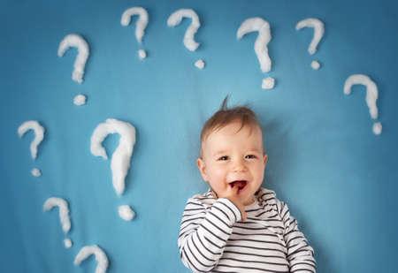 preguntando: divertido niño acostado en una manta azul con un montón de signos de interrogación