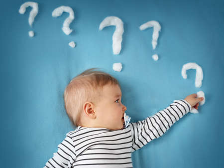funny little boy lying on blue blanket with lots of question marks