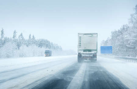 road conditions: Trucks moving on a motorway in blizzard