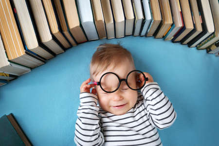 one year old: One year old baby among books with spectackle Stock Photo