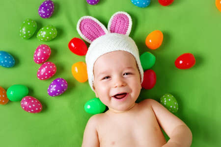 Baby boy in bunny hat lying on green blanket with multicolored easter eggs