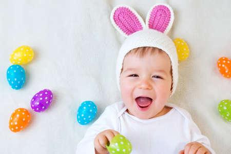 Baby boy en chapeau de lapin couché sur une couverture verte avec des oeufs de Pâques multicolores