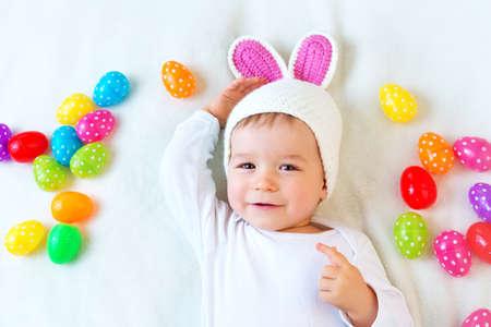 De jongen van de baby in konijntjeshoed liggend op groene deken met veelkleurige easter eggs