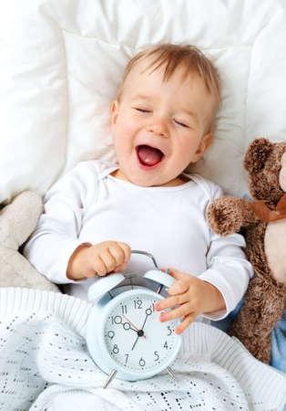 目覚まし時計とベッドで横になっている 1 歳の赤ちゃん