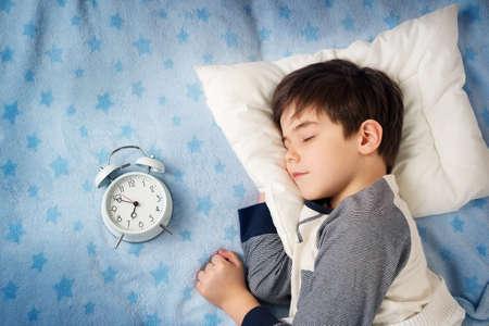 ni�o durmiendo: seis a�os del ni�o que duerme en cama en la almohadilla con el reloj de alarma