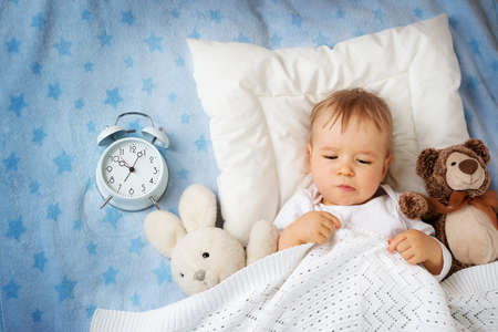 Een jaar oude baby liggend in bed met wekker