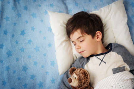 child: six years old child sleeping in bed on pillow with alarm clock and a teddy bear