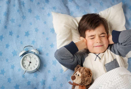 boy bedroom: six years old child sleeping in bed on pillow with alarm clock and a teddy bear