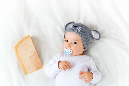 soother: Baby boy in mouse hat lying on blanket with big piece of cheese Stock Photo