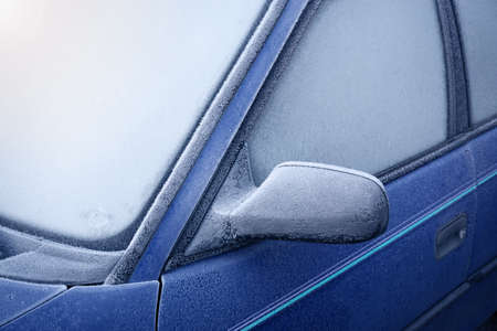 icy conditions: Car window and side mirror covered with ice in early morning