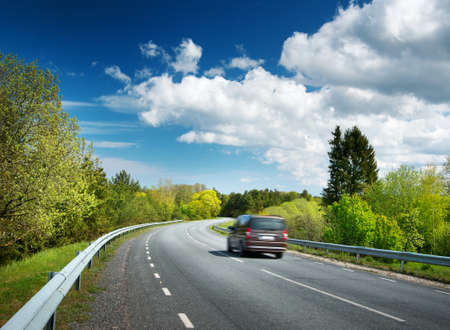 Car on asphalt road in beautiful spring day at countryside Banque d'images