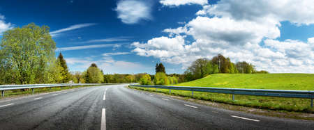 landscape background: asphalt road panorama in countryside on sunny spring day
