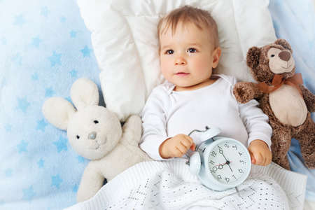 baby face: One year old baby lying in bed with alarm clock