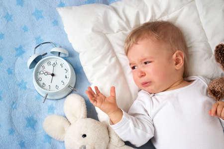 1 歳の赤ちゃんが泣いているとアラーム時計とベッドで横になっています。 写真素材