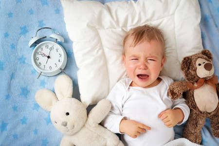 crying boy: Un año de edad bebé acostado en la cama con el despertador y el llanto