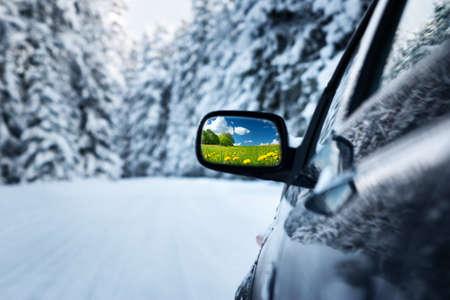 auto op de winter weg met zomer veld reflectie in de spiegel