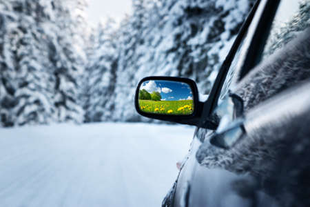 car on winter road with summer field reflection in mirror