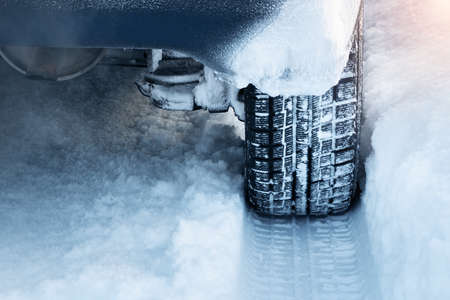 icy conditions: Closeup of car tires in winter on the road covered with snow Stock Photo