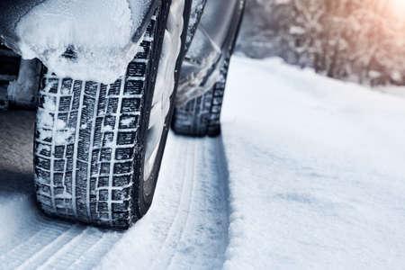 Primo piano di pneumatici per auto in inverno, sulla strada ricoperta di neve