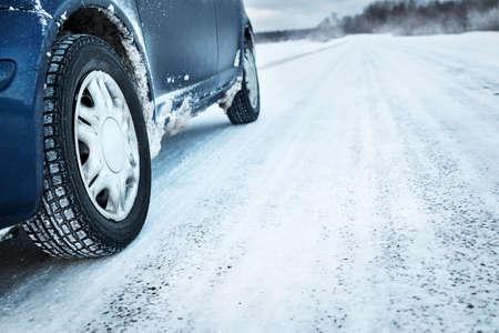 Close-up van autobanden in de winter op de weg bedekt met sneeuw