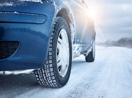 Closeup of car tires in winter on the road covered with snow Archivio Fotografico