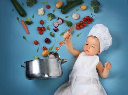 Neonato in cappello da cuoco con padella di cottura e verdure crude