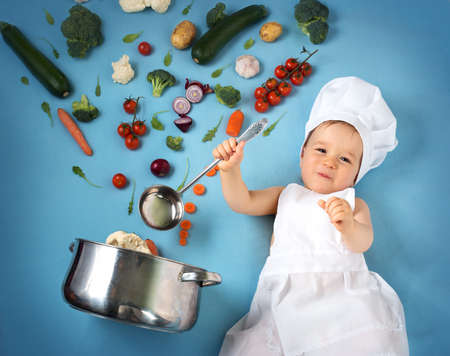 Baby boy in chef hat with cooking pan and raw vegetables Reklamní fotografie