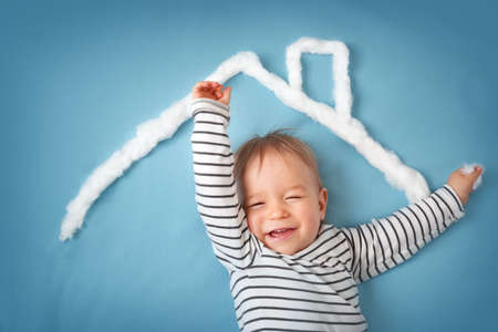protect family: little boy with shape of house roof on the blue background Stock Photo