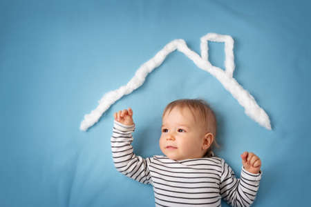 alone boy: little boy with shape of house roof on the blue background Stock Photo