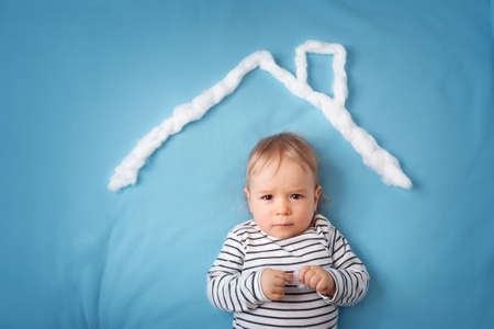 home security: little boy with shape of house roof on the blue background Stock Photo